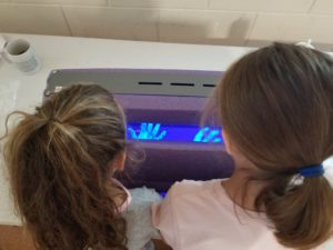 """Two 4-H'ers learn about proper hand hygiene by looking at their hands under a blacklight, while there is a special """"germ"""" lotion on their hands so they are able to see missed spots."""